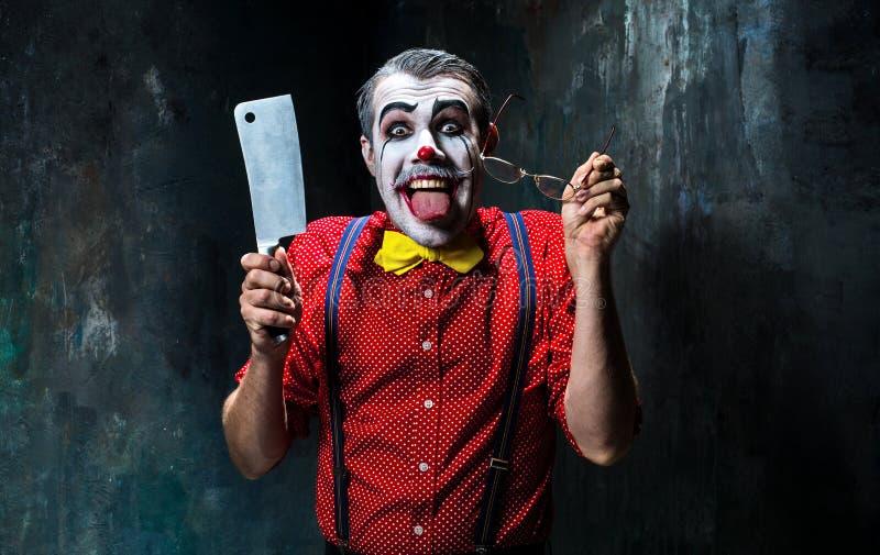 Ο τρομακτικός κλόουν που κρατά ένα μαχαίρι στο dack ημερολογιακής έννοιας ημερομηνίας ο απαίσιος μικροσκοπικός θεριστής εκμετάλλε στοκ φωτογραφίες
