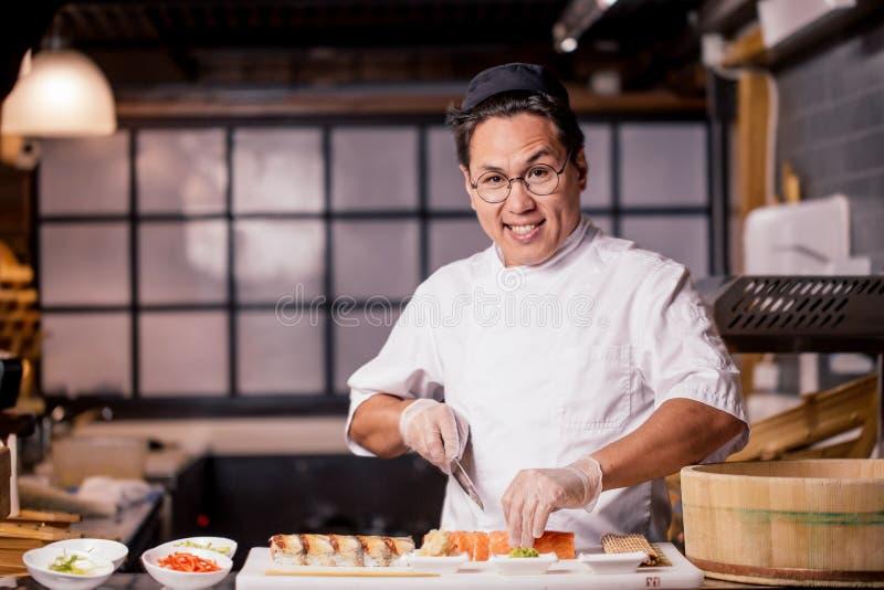 Ο τρομερός αρχιμάγειρας hansone εξετάζει τη κάμερα μαγειρεύοντας τα σούσια στοκ φωτογραφίες