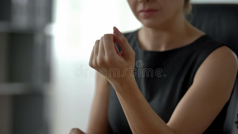 Ο τρυπώντας γραμματέας που εξετάζει τη νέες στιλβωτική ουσία, το μανικιούρ και την ομορφιά καρφιών της, κλείνει επάνω στοκ φωτογραφία