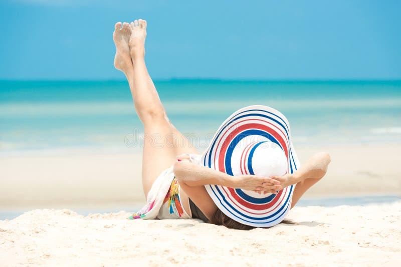 E Ο τρόπος ζωής που χαμογελά την ασιατική γυναίκα που φορά τα θερινά ταξίδια μόδας μπικινιών χαλαρώνει στην αμμώδη ωκεάνια παραλί στοκ εικόνες