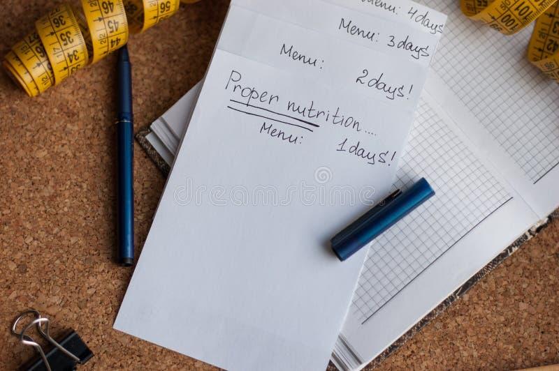 Ο τρόπος ζωής, σημειωματάριο για τις επιλογές, κατάλληλα τρόφιμα, η λαβή είναι φελλός-βασισμένος γράψτε ένα σχέδιο για την εβδομά στοκ εικόνες με δικαίωμα ελεύθερης χρήσης