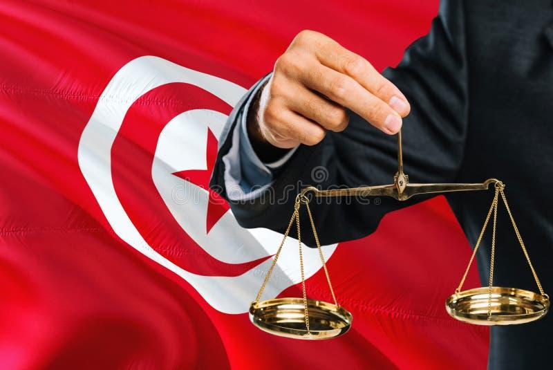 Ο τυνησιακός δικαστής κρατά τις χρυσές κλίμακες της δικαιοσύνης με το κυματίζοντας υπόβαθρο σημαιών της Τυνησίας Θέμα ισότητας κα στοκ φωτογραφίες