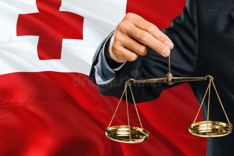 Ο των νήσων Τόγκα δικαστής κρατά τις χρυσές κλίμακες της δικαιοσύνης με τα Τόνγκα που κυματίζουν το υπόβαθρο σημαιών Θέμα ισότητα στοκ φωτογραφίες