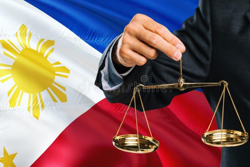 Ο των Φηληππίνων δικαστής κρατά τις χρυσές κλίμακες της δικαιοσύνης με το κυματίζοντας υπόβαθρο σημαιών των Φιλιππινών Θέμα ισότη στοκ εικόνες με δικαίωμα ελεύθερης χρήσης