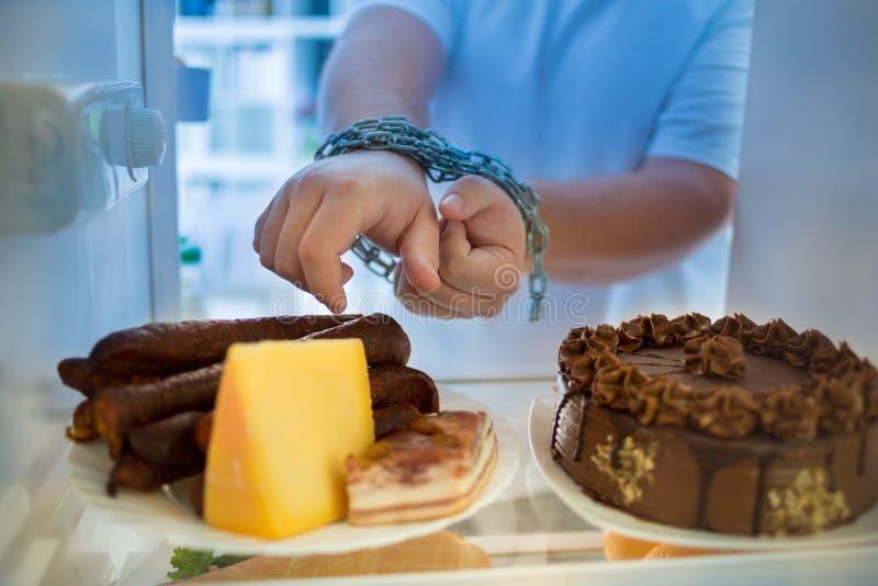 Ο τύπος έχει τη νύχτα την κρίση διατροφής και επιθυμεί να φάει τα λουκάνικα στοκ εικόνα