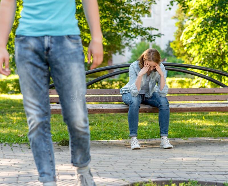 Ο τύπος αφήνει το νέο κορίτσι Αυτό το πάρκο είναι στη φύση Ένα κορίτσι είναι λυπημένο και να φωνάξει κάθεται σε έναν πάγκο Η έννο στοκ φωτογραφίες