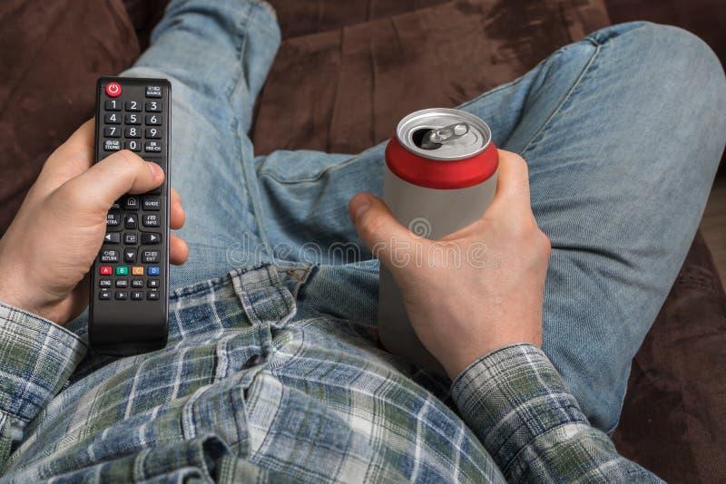 Ο τύπος βρίσκεται στον καναπέ με την μπύρα τηλεχειρισμού και κατανάλωσης TV στοκ φωτογραφία