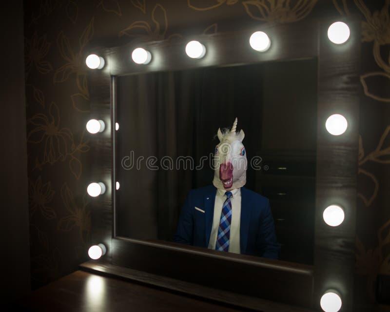 Ο τύπος γοητείας στο κοστούμι και τη μάσκα εξετάζει τον στοκ εικόνα