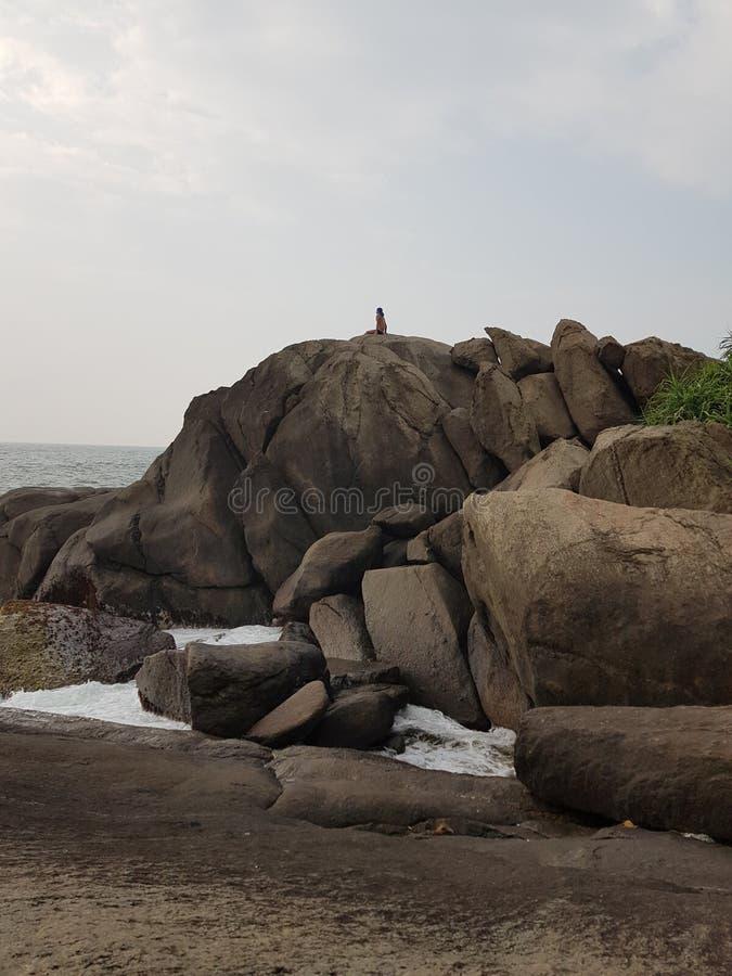Ο τύπος εξετάζει τον ωκεανό, καθμένος στις τεράστιες πέτρες στοκ φωτογραφία με δικαίωμα ελεύθερης χρήσης