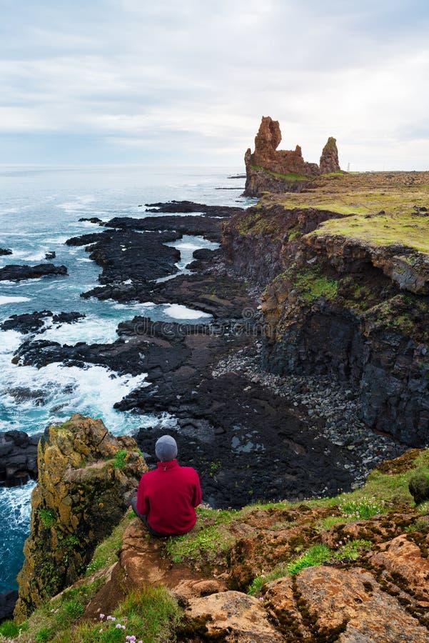 Ο τύπος εξετάζει τους βράχους Londrangar στην Ισλανδία στοκ εικόνες