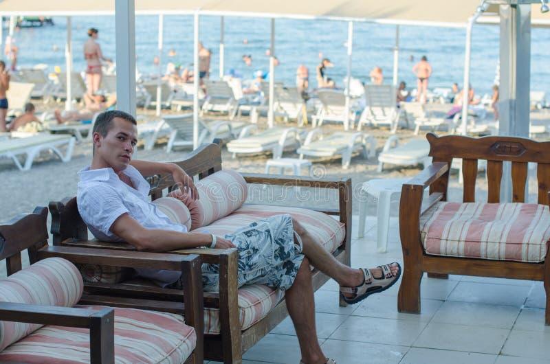 Ο τύπος κάθεται κοντά στην παραλία στα ενδύματα Το νέο κουρασμένο άτομο στηρίζεται τη συνεδρίαση σε έναν πάγκο θαλασσίως μετά από στοκ φωτογραφίες
