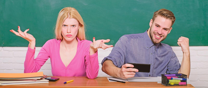 Ο τύπος και το κορίτσι ξένοιαστοι κάθονται στο γραφείο στην τάξη Μελέτη στο κολλέγιο ή το πανεπιστήμιο Σπουδαστές φίλων που μελετ στοκ εικόνα με δικαίωμα ελεύθερης χρήσης