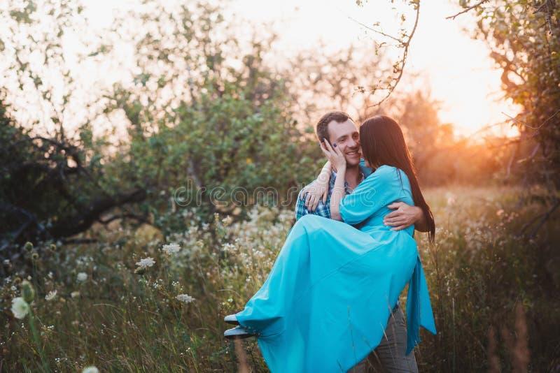 Ο τύπος και το κορίτσι που στέκονται στη φύση, αγκαλιάζουν και φιλούν κάτω από την ενδυμασία ενός ευρέος καπέλου στοκ φωτογραφίες