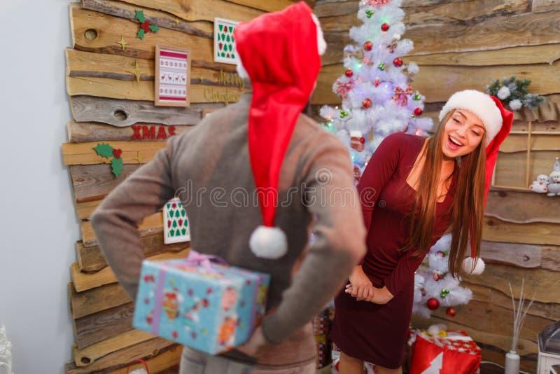 Ο τύπος κρατά ένα κιβώτιο δώρων πίσω από την πλάτη του, και το κορίτσι εξετάζει το πίσω μέρος του τύπου indoors στοκ εικόνα