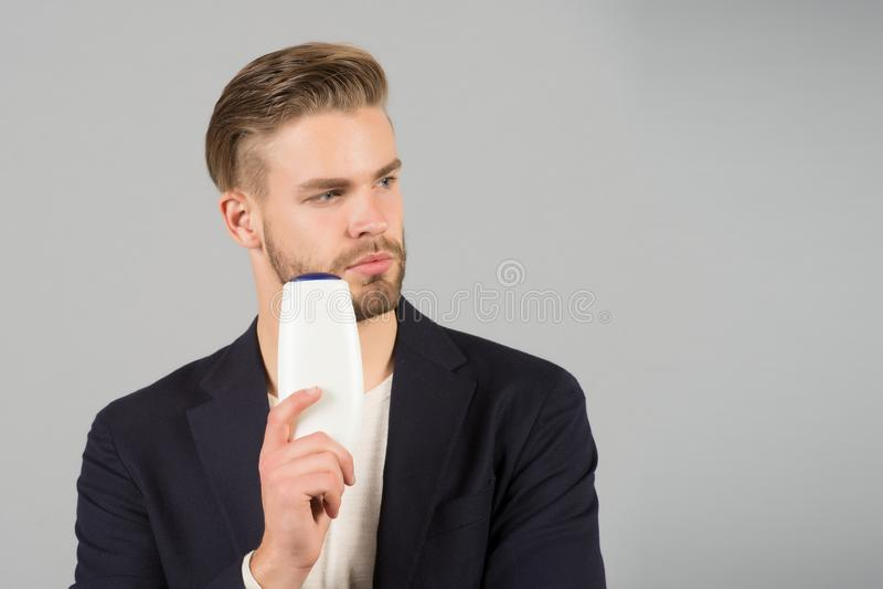 Ο τύπος με τη σκληρή τρίχα κρατά το σαμπουάν μπουκαλιών, διάστημα αντιγράφων Το άτομο απολαμβάνει τη φρεσκάδα μετά από να πλύνει  στοκ εικόνα