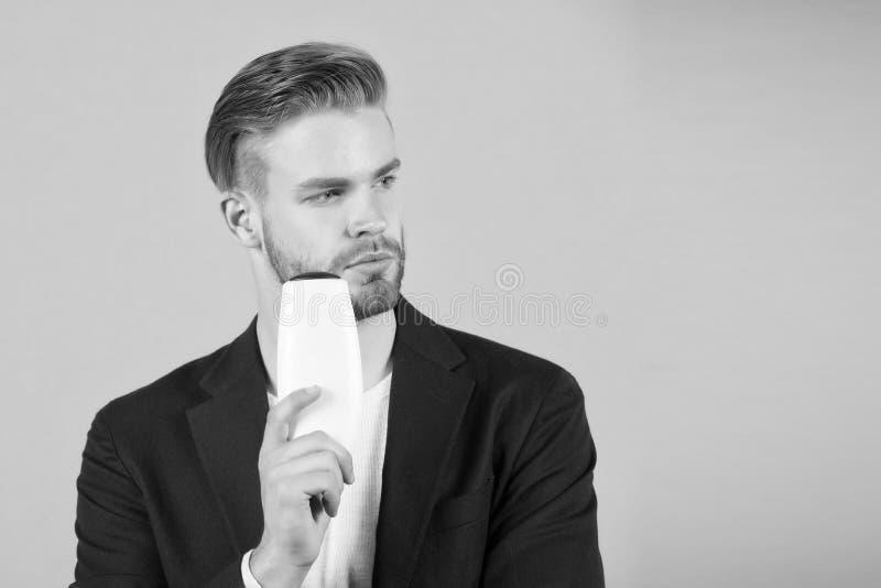 Ο τύπος με τη σκληρή τρίχα κρατά το σαμπουάν μπουκαλιών, διάστημα αντιγράφων Το άτομο απολαμβάνει τη φρεσκάδα μετά από να πλύνει  στοκ εικόνες με δικαίωμα ελεύθερης χρήσης