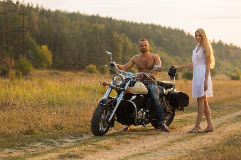 Ο τύπος με το κορίτσι σε έναν τομέα σε μια μοτοσικλέτα στοκ φωτογραφίες