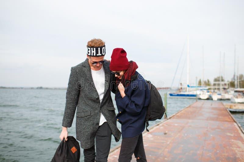 Ο τύπος με το κορίτσι στην αποβάθρα το κορίτσι οδηγά skateboard στοκ φωτογραφίες με δικαίωμα ελεύθερης χρήσης