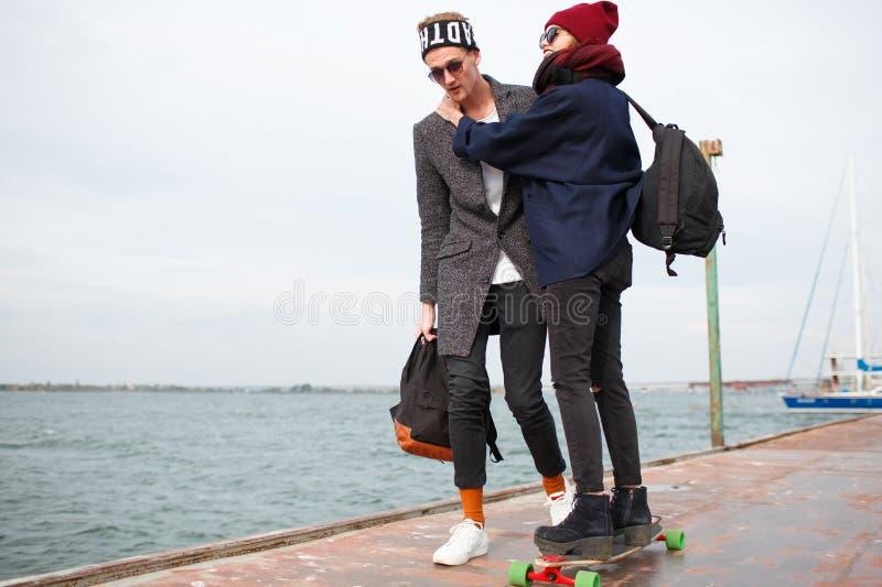 Ο τύπος με το κορίτσι στην αποβάθρα το κορίτσι οδηγά skateboard στοκ φωτογραφίες