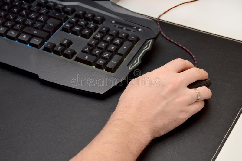 Ο τύπος παίζει ένα τηλεοπτικό παιχνίδι Κλείστε επάνω ενός χεριού σε ένα ποντίκι και ένα μαύρο πληκτρολόγιο τυχερού παιχνιδιού σε  στοκ εικόνες