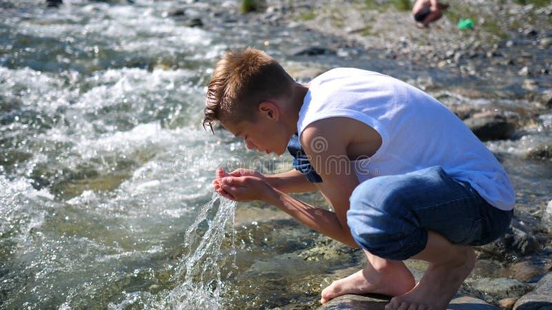 Ο τύπος πλένεται κρύο νερό βουνών Ταξιδιώτης ξημερωμάτων στοκ φωτογραφίες με δικαίωμα ελεύθερης χρήσης