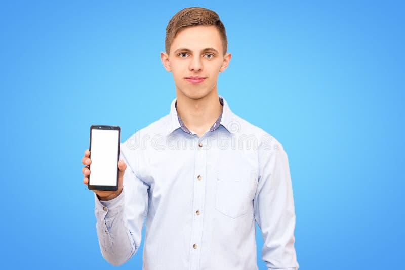 Ο τύπος που φορά το μπλε πουκάμισο διαφημίζει το τηλέφωνο στοκ εικόνες