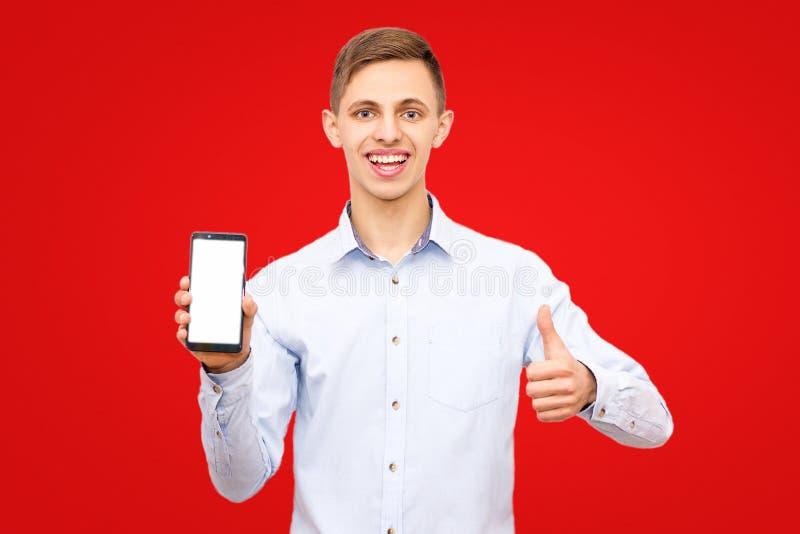 Ο τύπος σε ένα μπλε πουκάμισο διαφημίζει ένα τηλέφωνο που απομονώνεται σε ένα κίτρινο υπόβαθρο στο στούντιο στοκ φωτογραφία