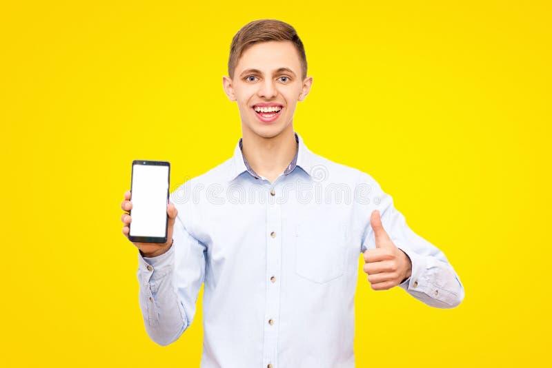 Ο τύπος σε ένα μπλε πουκάμισο διαφημίζει ένα τηλέφωνο που απομονώνεται σε ένα κίτρινο υπόβαθρο στο στούντιο στοκ εικόνες