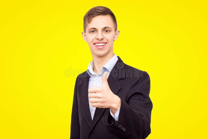 Ο τύπος σε ένα σακάκι και ένα μπλε πουκάμισο παρουσιάζει ένα δάχτυλο που απομονώνεται επάνω σε ένα κίτρινο υπόβαθρο στοκ φωτογραφία με δικαίωμα ελεύθερης χρήσης