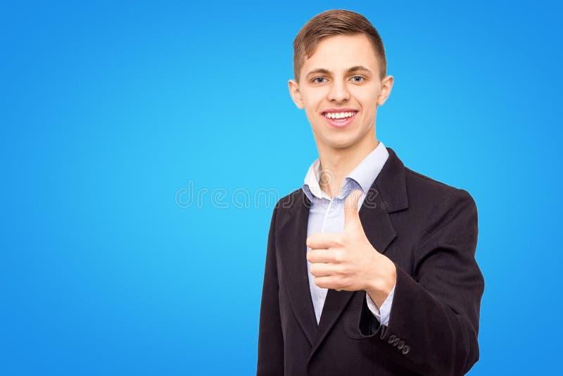 Ο τύπος σε ένα σακάκι και ένα μπλε πουκάμισο παρουσιάζει δάχτυλό του που απομονώνεται επάνω σε ένα μπλε υπόβαθρο στοκ εικόνα με δικαίωμα ελεύθερης χρήσης