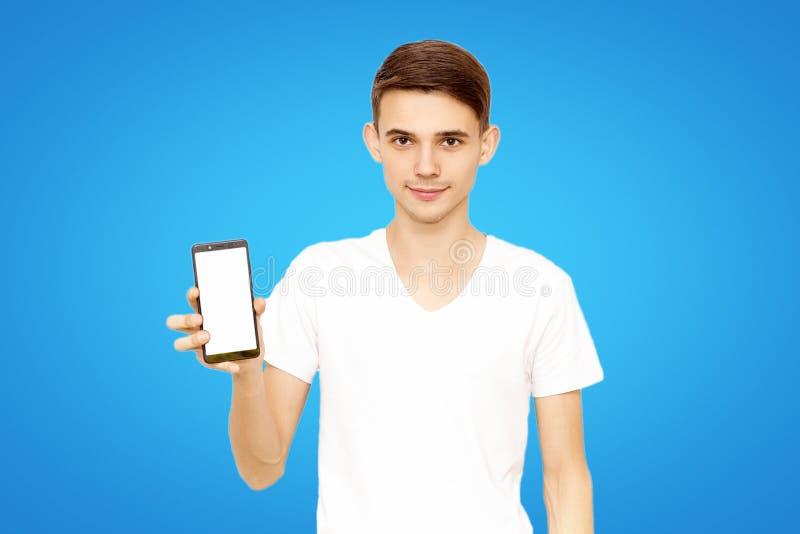 Ο τύπος στην άσπρη μπλούζα διαφημίζει το τηλέφωνο, σε ένα μπλε υπόβαθρο στο στούντιο στοκ εικόνα