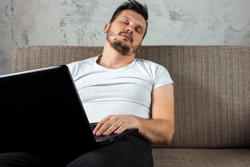Ο τύπος στην άσπρη συνεδρίαση πουκάμισων στον καναπέ, έπεσε κοιμισμένος στην εργασία για ένα lap-top Η έννοια της τεμπελιάς, απάθ στοκ εικόνες