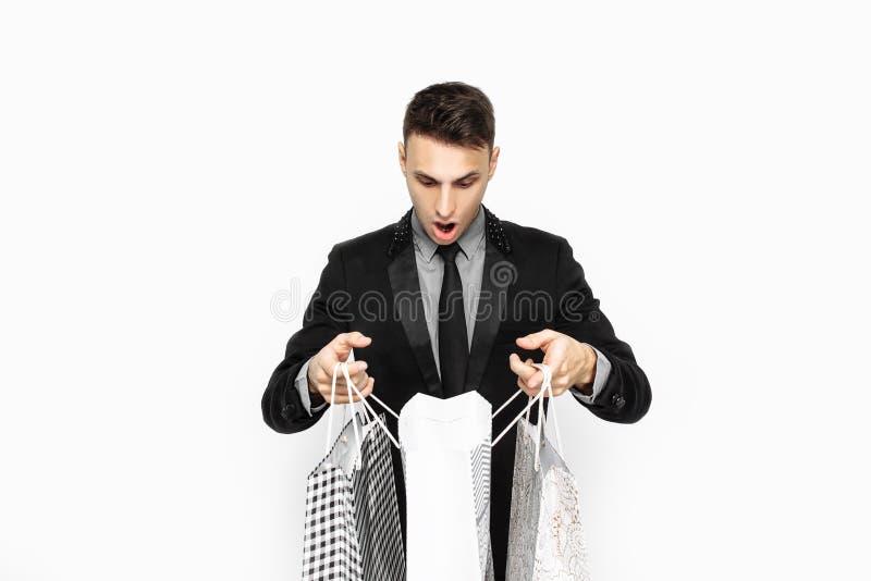Ο τύπος στο μαύρο κομψό κοστούμι, που ψωνίζει στην εποχή πωλήσεων στοκ φωτογραφία