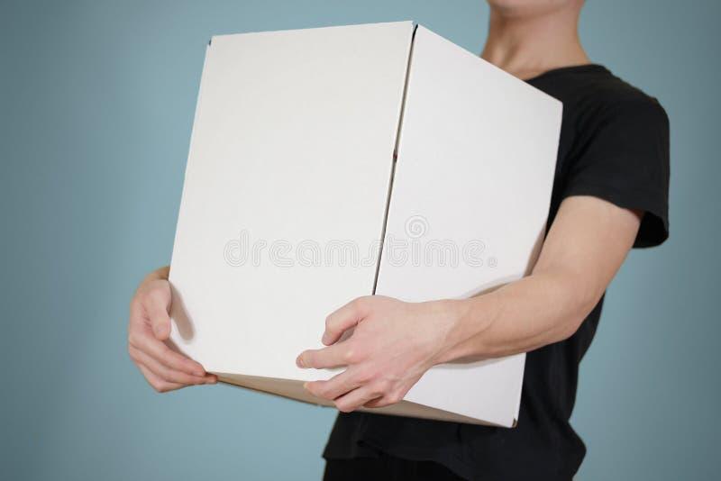 Ο τύπος στο μαύρο πουκάμισο που κρατά ένα μεγάλο άσπρο κιβώτιο Φέρνει το α στοκ φωτογραφία