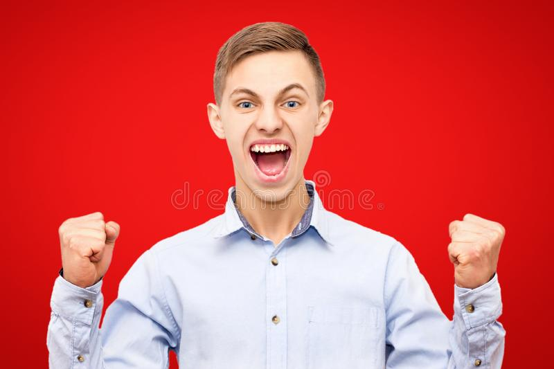 Ο τύπος στο μπλε πουκάμισο χαίρεται τη νίκη που απομονώνεται στο κόκκινο υπόβαθρο, αυξημένα χέρια επάνω στοκ φωτογραφίες