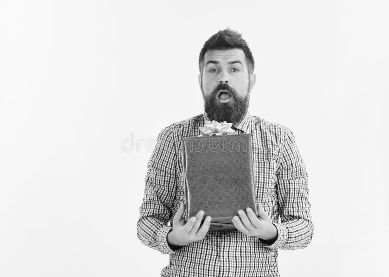 Ο τύπος στο πουκάμισο καρό κρατά το παρόν κιβώτιο Φαλλοκράτης με το τυλιγμένο μπλε δώρο και το άσπρο τόξο Άτομο με τη γενειάδα κα στοκ εικόνα