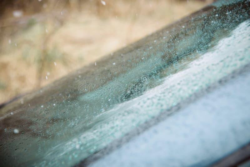 Ο υγροί ανεμοφράκτης αυτοκινήτων κινηματογραφήσεων σε πρώτο πλάνο και η ψήκτρα ανεμοφρακτών με τη βροχή μειώνονται στη βρέχοντας  στοκ φωτογραφίες