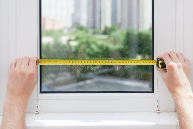 Ο υπάλληλος κάνει μια μέτρηση του γυαλιού σε ένα πλαστικό παράθυρο χρησιμοποιώντας ένα μέτρο ταινιών στοκ φωτογραφίες