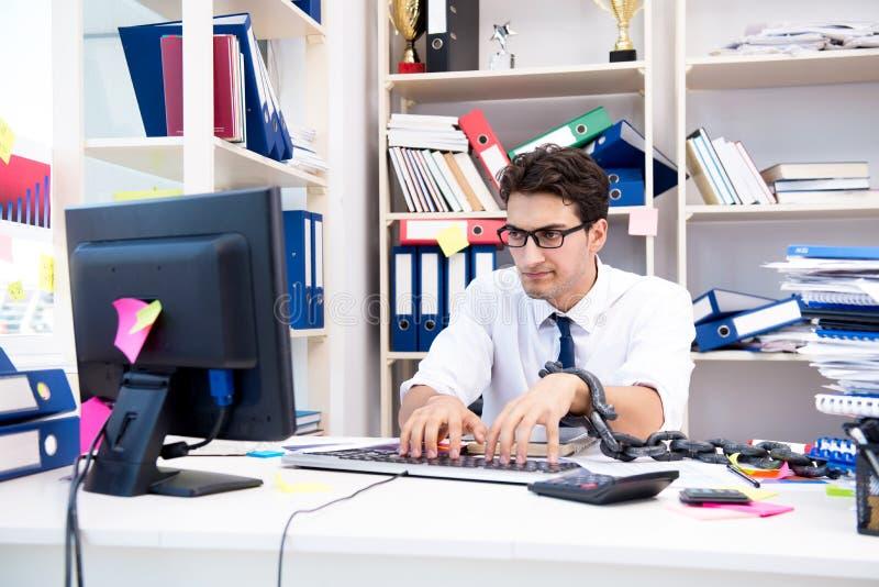 Ο υπάλληλος συνδέθηκε και αλυσόδεσε στο γραφείο του με την αλυσίδα στοκ εικόνες με δικαίωμα ελεύθερης χρήσης