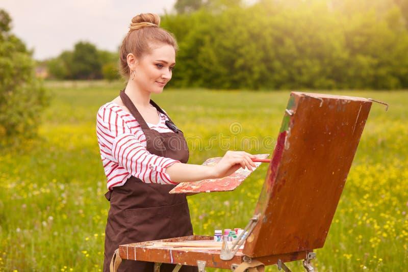 Ο υπαίθριος πυροβολισμός του καλλιτέχνη νέων κοριτσιών χρωματίζει την εικόνα σε υπαίθριο Μάθημα ζωγραφικής στη φύση Ελκυστικός ξα στοκ εικόνες