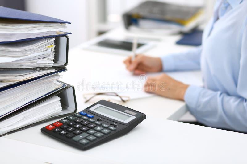 Ο υπολογιστής και οι σύνδεσμοι με τα έγγραφα περιμένουν να υποβληθούν σε επεξεργασία από την επιχειρησιακό γυναίκα ή το λογιστή π στοκ εικόνες