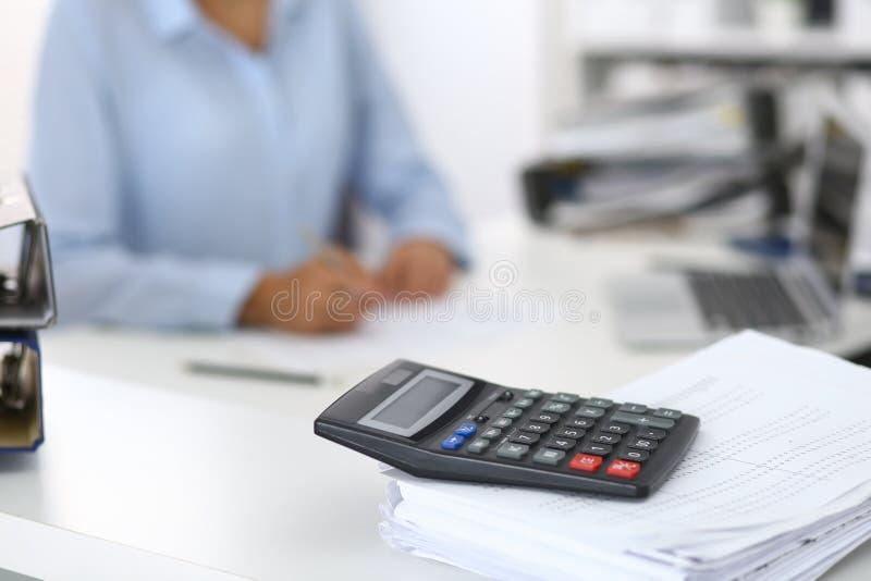 Ο υπολογιστής και οι σύνδεσμοι με τα έγγραφα περιμένουν να υποβληθούν σε επεξεργασία από την επιχειρησιακό γυναίκα ή το λογιστή π στοκ φωτογραφία