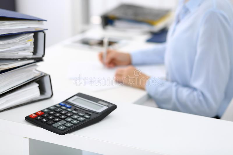 Ο υπολογιστής και οι σύνδεσμοι με τα έγγραφα περιμένουν να υποβληθούν σε επεξεργασία από την επιχειρησιακό γυναίκα ή το λογιστή π στοκ φωτογραφίες