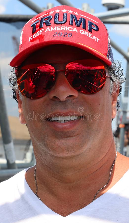 Ο υποστηρικτής Προέδρου Donal Trump φορά το διάσημο κόκκινο καπέλο με το ατού σημαδιών κρατά την Αμερική μεγάλο το 2020 στοκ φωτογραφία με δικαίωμα ελεύθερης χρήσης
