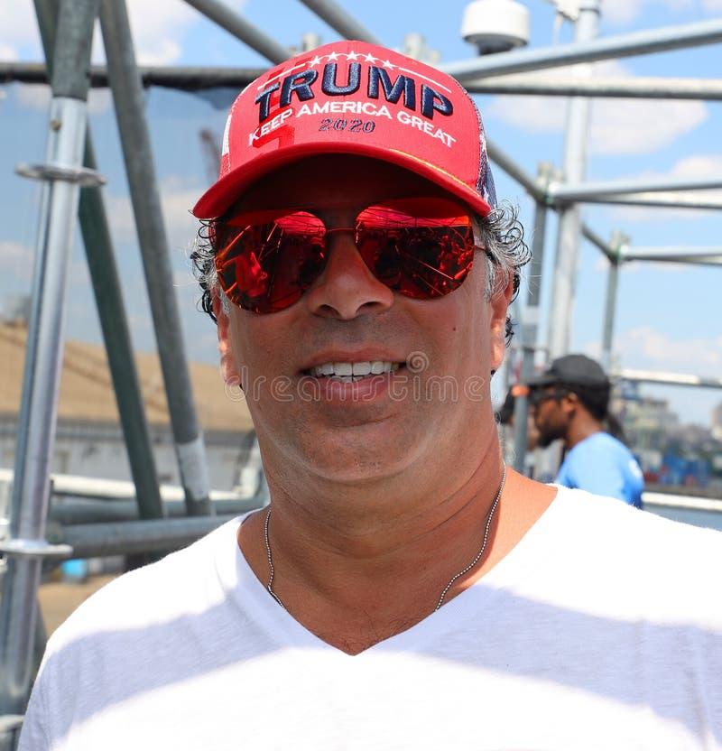 Ο υποστηρικτής Προέδρου Donal Trump φορά το διάσημο κόκκινο καπέλο με το ατού σημαδιών κρατά την Αμερική μεγάλο το 2020 στοκ φωτογραφία