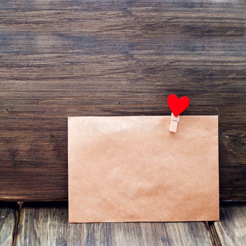 Ο φάκελος του συνδετήρα εγγράφου της Kraft με μορφή μιας καρδιάς σε ένα ξύλινο υπόβαθρο, ημέρα βαλεντίνων ` s, τοποθετήσεις ανθρώ στοκ φωτογραφία με δικαίωμα ελεύθερης χρήσης