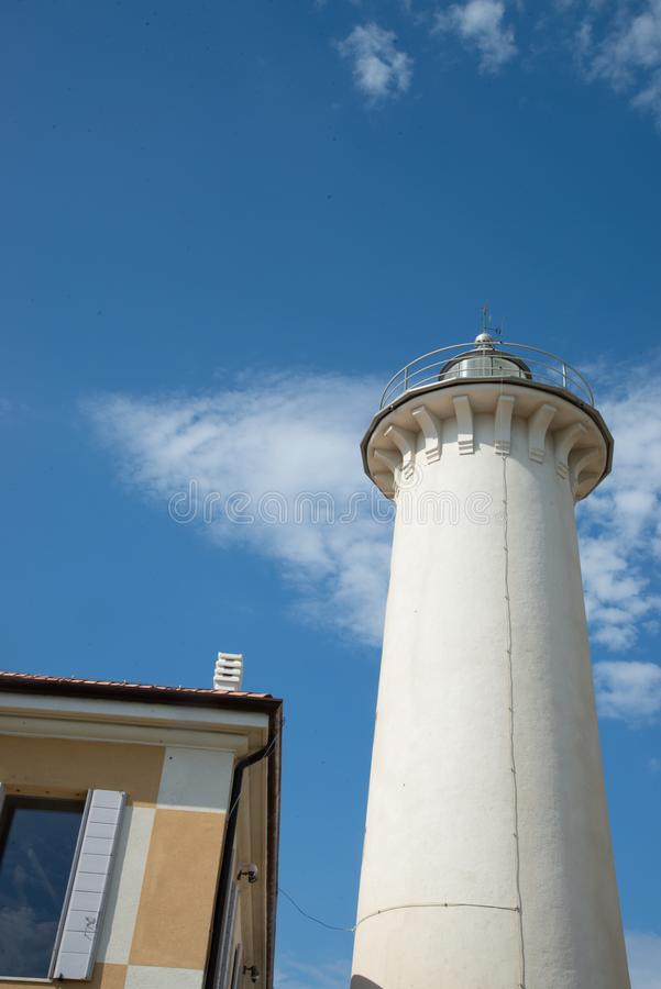 Ο φάρος Bibione, Βένετο, Ιταλία, στο υπόβαθρο ένας όμορφος μπλε ουρανός με τα άσπρα σύννεφα στοκ εικόνες