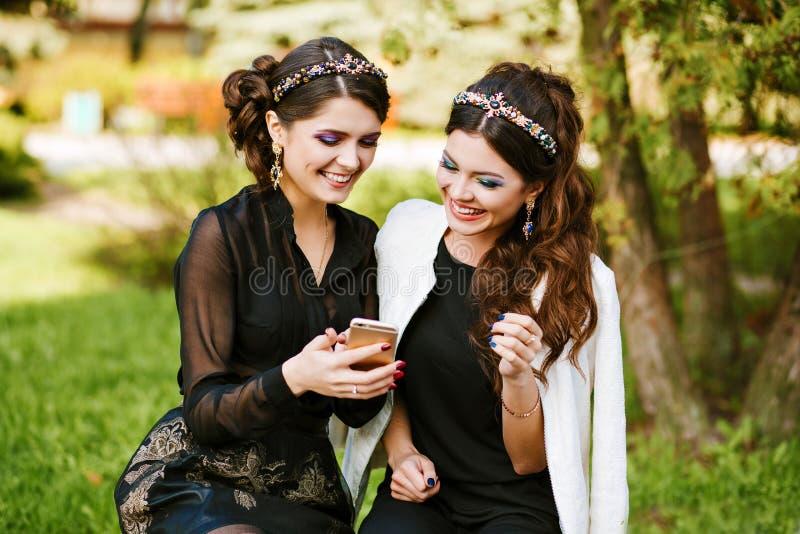 Ο φίλος εξετάζει το τηλέφωνο και συζητά κάτι Γέλιο και χαμόγελο, μετάβαση τρελλή, έχοντας τη διασκέδαση Νέα μοντέρνη γυναίκα στοκ εικόνα