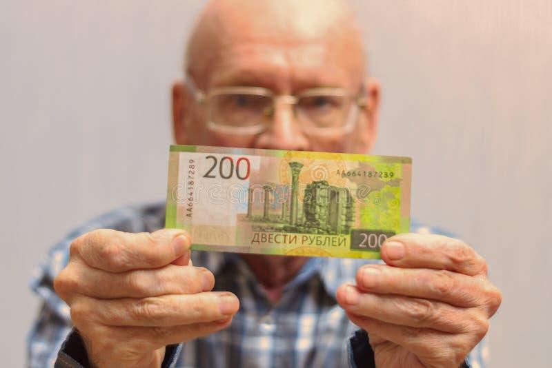 Ο φαλακρός ηληκιωμένος με τα γυαλιά κρατά ένα τραπεζογραμμάτιο 200 ρουβλιών μπροστά από τον στοκ φωτογραφία
