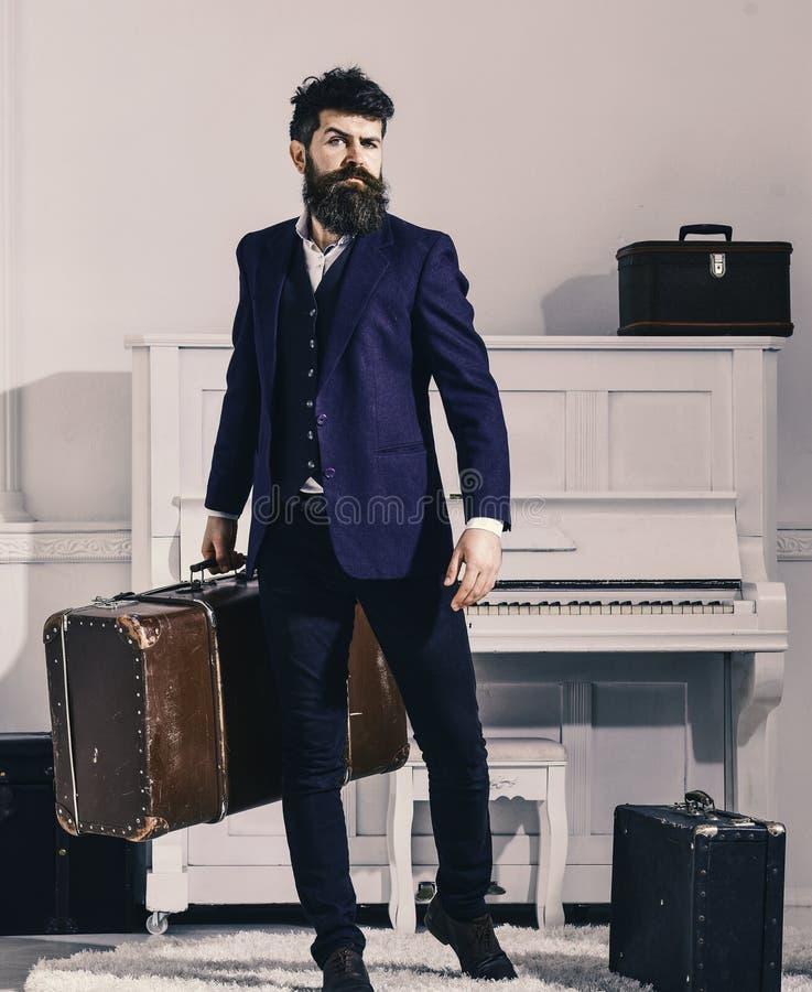 Ο φαλλοκράτης μοντέρνος στο ακριβές πρόσωπο στέκεται και φέρνει τη μεγάλη εκλεκτής ποιότητας βαλίτσα Αποσκευές και διακινούμενη έ στοκ φωτογραφία με δικαίωμα ελεύθερης χρήσης